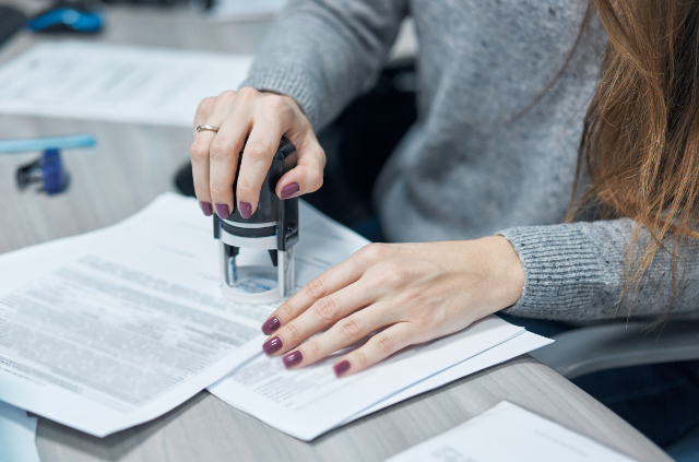 woman puts a stamp on documents in the office